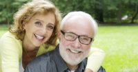 An older couple smiling after discovering the cost of CEREC crowns at Bawa Dentistry